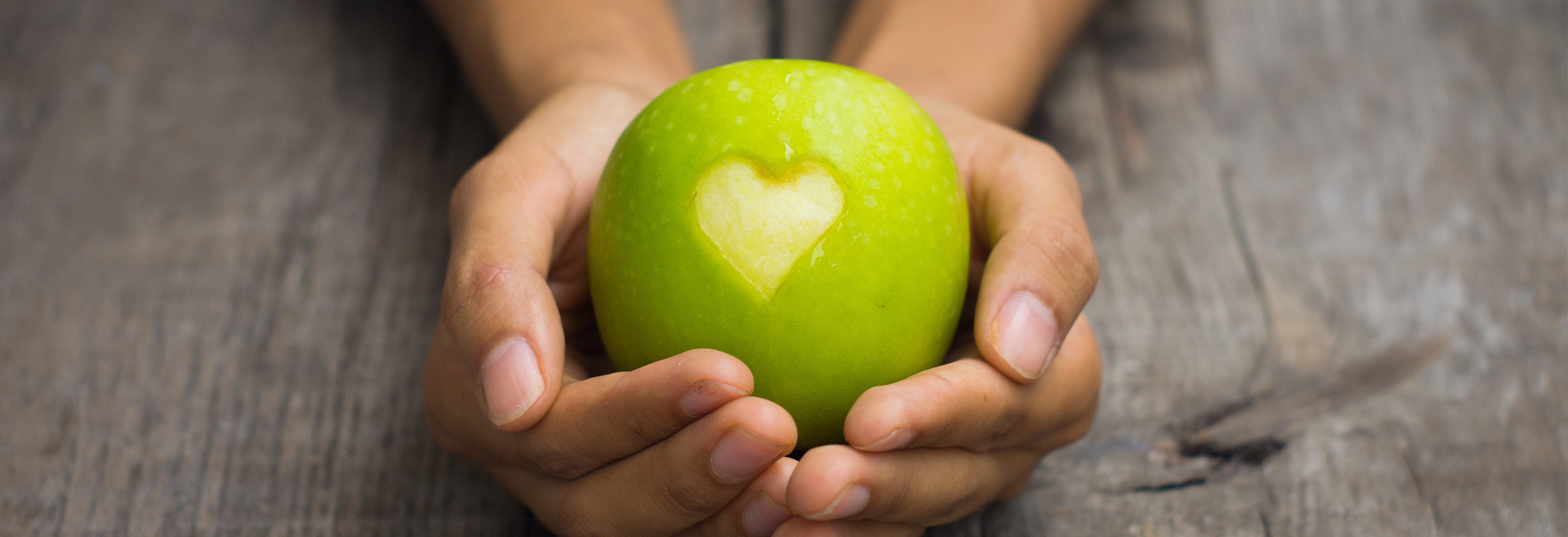Hands cradling a green apple with a heart shapped bit missing.
